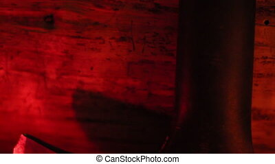 Upside view of an axe under a red-lighted room