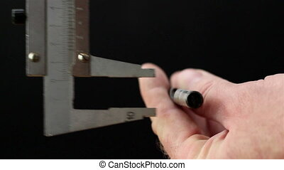 A caliper getting the measurement of the screw - A caliper...