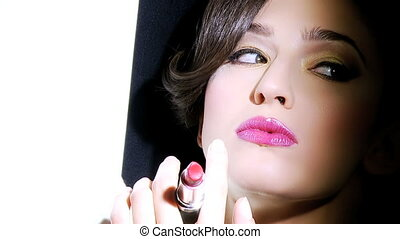 Female model playing with lipstick