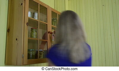 Woman cabinet canned food - Woman hands take glass jar with...