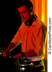 Disc jockey working in colourful party light - Disc jockey...