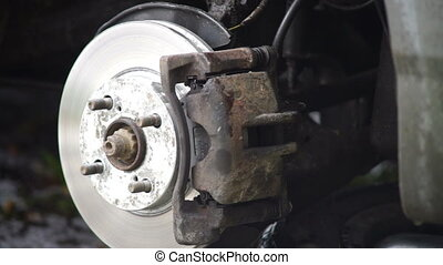 Man taking off brake caliper - Changing a car wheel: driver...