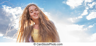 Portrait of happy woman smiling against clear sky