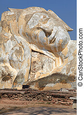 part of giant reclining buddha statue at temple ruin over...