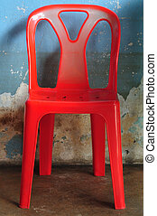 Old red plastic chair in front of blue wall.