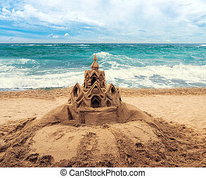 Sand castle on beach with water from wave