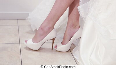 Wedding shoes - Bride is trying on her wedding dress and...
