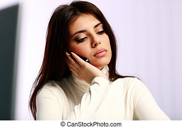 Closeup portrait of a young pensive woman talking on the phone