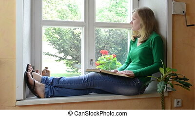 girl read book sill - serious face girl sit on windowsill...