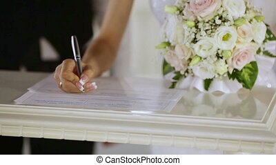 Signing the Register - A groom and fiancee sign