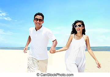 Portrait of beach couple in white dress running having fun...