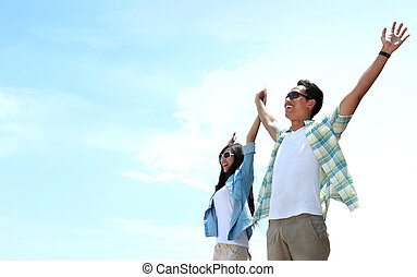 Asian Young couple standing and raised their hands to the...