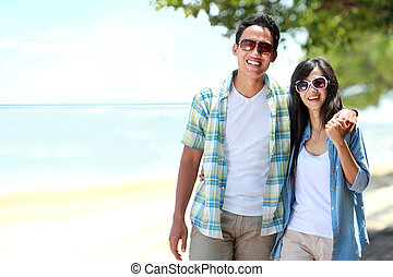 Portrait of happy couple walking by the beach together in love holding around each other