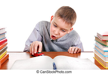 Schoolboy plays with a Toy on the School Desk on the white...