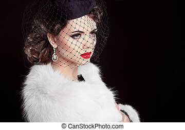Fashion Brunette Model Portrait. Jewelry and Hairstyle. Elegant lady wearing in white fur coat Isolated on black background.
