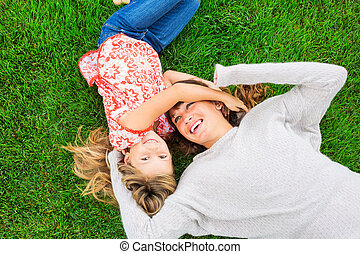 Mother and daughter lying together outside on grass -...