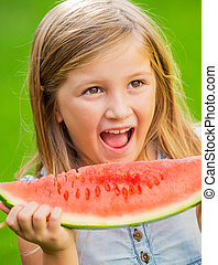 Adorable blonde girl eating watermelon outdoors - Adorable...