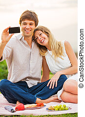Couple taking photo of themselves with smartphone on picnic...