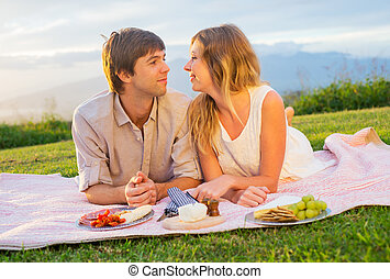 Attractive couple on romantic sunset picnic in countryside