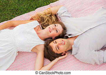 Romantic picnic in the park, loving couple on blanket...