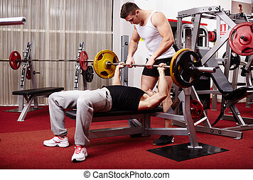 Young man lifting the barbell with help - Young athletic...