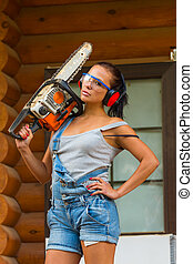 Pretty young woman builder with powered chain saw