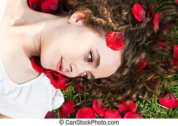 Beautiful woman in rose petals