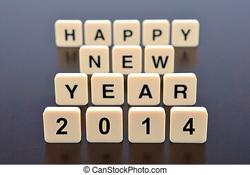 Happy New Year 2014 word formed by letter pieces, focus pointed at the front and shallow DOF