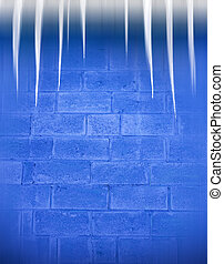 Icicles on a roof against a dark blue brick wall