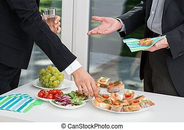 Business people having meal together - Business people...