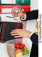 Manager with healthy meal - Manager sitting at desk with...