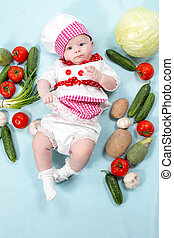 Baby cook girl wearing chef hat with fresh vegetables. Use...
