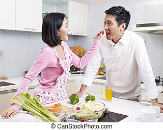 asian couple in kitchen - romantic asian couple preparing...