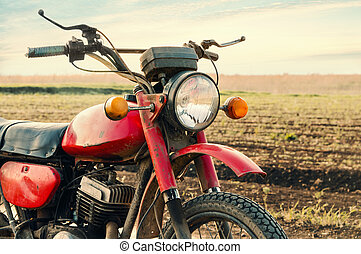 Classic old motorcycle on a dirt road