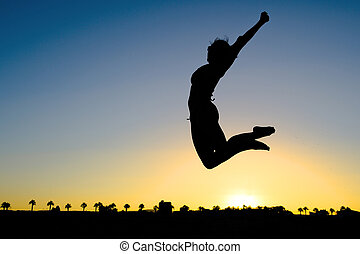 Woman Silhouette Jumping on the Beach at Sunset transmitting...