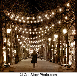 Silhouette of girl walking by night alley. Vintage style