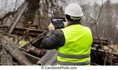 Building Inspector with tablet PC near collapsed building...