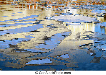 floating thin ice on the river - sunlit drifting ice floe on...
