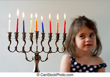 Hanukkah menorah - Cute Jewish girl look at fully lit...