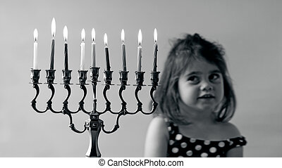 Hanukkah menorah - Jewish girl look at fully lit Hanukkah...