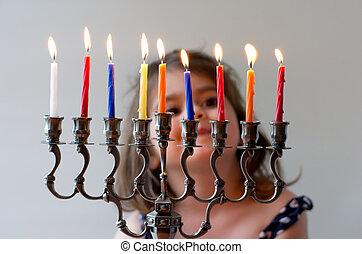 Hanukkah menorah - Happy Jewish girl look at fully lit...