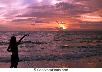 woman silhouette pointing in the sunset