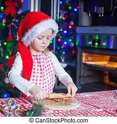 Portrait of little girl with rolling pin baking Christmas...