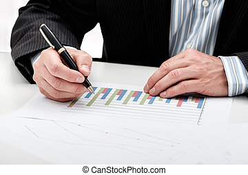 Bar chart analysis - A man analysing a bar chart writing...
