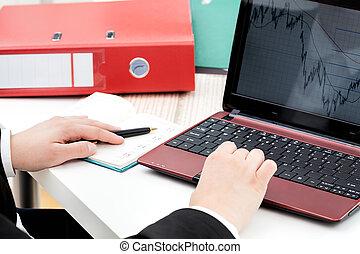 Line chart analyzing - Analyzing line chart at a laptop...