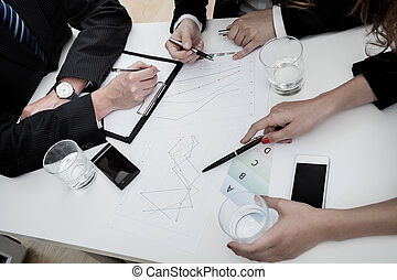 Business table - Three businessmen working by a big white...