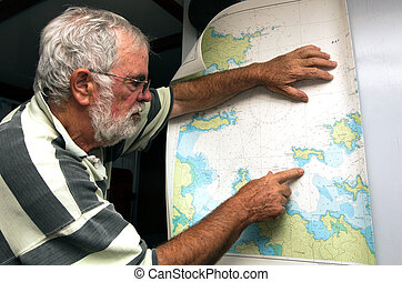 Sailor reads a sea map in his boat.