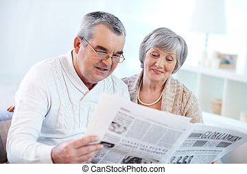 Reading news - Portrait of happy mature couple sitting at...