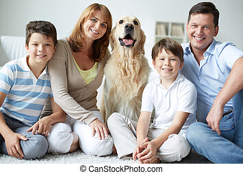 Togetherness - Portrait of happy family with fluffy Labrador...