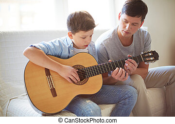 Playing guitar - Portrait of handsome young man teaching his...